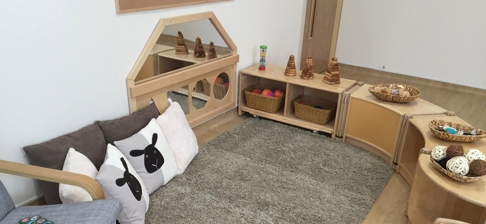 Cosy area in our Buttercup Room with pillows, toys and mirrors.