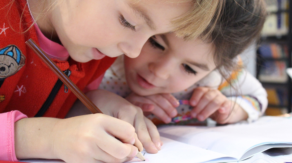 Two children drawing with pencils