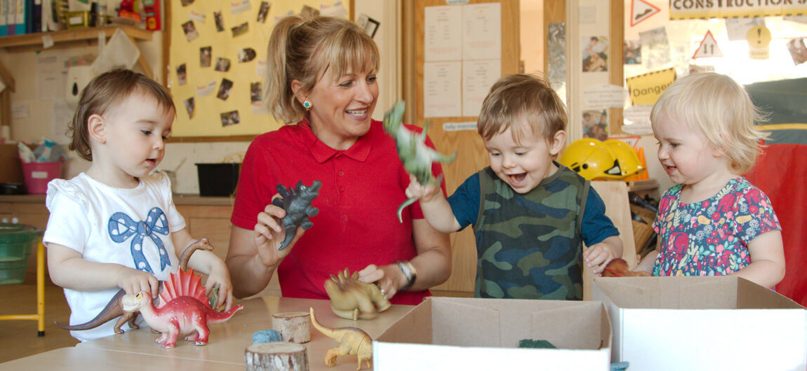 Children and staff in our Daisy room playing with dinosaur toys